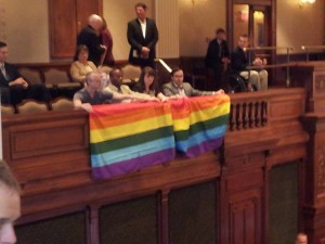 "Left-wing Chicago homosexual activist Andy Thayer of Gay Liberation Network (GLN) unfurls homosexualist ""rainbow flag"" in the gallery of the Illinois House yesterday. Photo: Dave Smith of Illinois Family Institute -- who reports that the Illinois ""gay"" lobby is still a few votes shy to pass homosexuality-based ""marriage"" before the session ends Friday, May 31.."