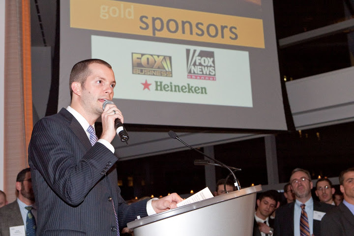 "Fox News Channel and Fox Business Channel are shown on a big screen as ""Gold"" sponsors of the NLGJA's 2009 New York City fundraiser, ""Headlines & Headliners."" Speaking in the foreground is NBC's Javier Morgado, a ""Today"" Show producer and longtime NLGJA official. Photo: NLGJA."